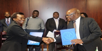Ambassador Chitsaka Chipaziwa, shakes hands with International Organisation for Migration Chief of Mission, Ms Lily Sanya, at the hand-over ceremony of a Video-Conferencing facility